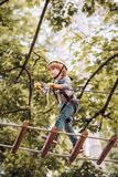 Child playing on the playground. Cute school child boy enjoying a sunny day in a climbing adventure activity park. Happy. Child boy calling while climbing high stock image
