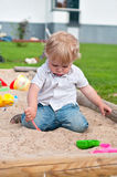 Child playing on playground in sandbox Stock Image