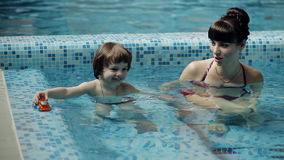 Child playing in the pool with his mother stock video