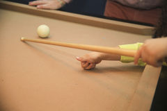 Child Playing Pool. A young child is learning how to play pool. He has his thumb in position and getting ready to aim Stock Image