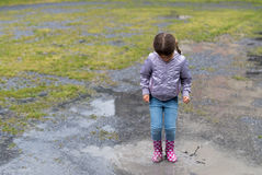 The child playing in a puddle Royalty Free Stock Photos