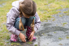 The child playing in a puddle Stock Image