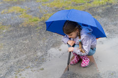 The child playing in a puddle Stock Images