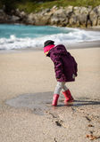 Child playing in puddle on sandy beach of Atlantic ocean. stock image