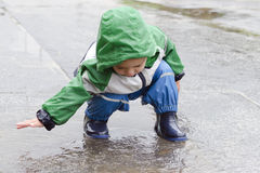 Child playing in puddle Stock Photo