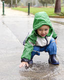 Child playing in puddle Royalty Free Stock Image