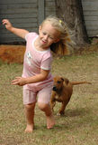 Child playing with puppy. A cute little blond caucasian girl with happy smiling facial expression playing with a dog. She is running away from her Rhodesian Royalty Free Stock Images