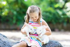 Child with rabbit. Easter bunny. Kids and pets. Child playing with rabbit. Little girl feeding white bunny. Easter celebration. Egg hunt with kid and pet animal Royalty Free Stock Images