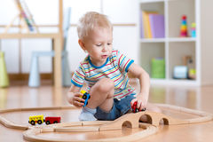 Child playing rail road toy in nursery Royalty Free Stock Photo