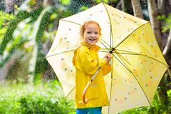 Child playing in the rain. Kid with umbrella royalty free stock photos