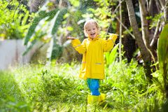 Child playing in the rain. Kid with umbrella stock image