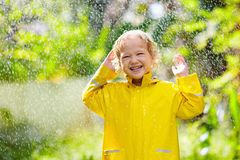 Child playing in the rain. Kid with umbrella stock images