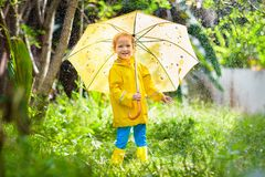 Child playing in the rain. Kid with umbrella royalty free stock images