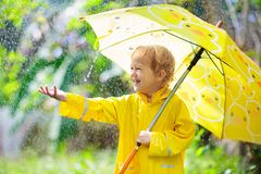 Child playing in the rain. Kid with umbrella royalty free stock image