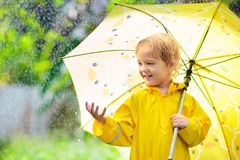 Child playing in the rain. Kid with umbrella royalty free stock photo