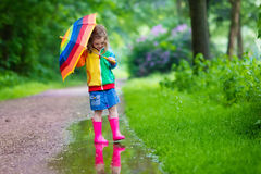 Child playing in the rain Stock Images