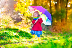 Child playing in the rain with umbrella in autumn park Royalty Free Stock Photography