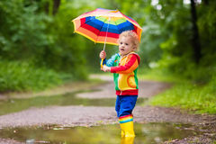 Child playing in the rain under umbrella royalty free stock photo