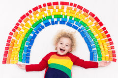 Child playing with rainbow plastic blocks toy Stock Photography