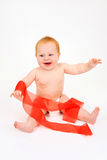 The child playing with a red ribbon Royalty Free Stock Images