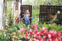 A child playing with red tulips in the garden Stock Image