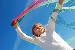 Child playing with ribbons. Little girl playing with bright ribbons in the sky Stock Photography