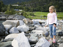 Child playing on rocks. Cute young girl with blond hair walking on rocks and boulders; green countryside background Royalty Free Stock Images