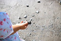 Child playing with rocks on the beach. Little girl holding a pebble at the beach Royalty Free Stock Photos