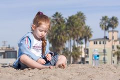 Child playing with sand on a beach. 4 years old girl playing with sand on a beach Stock Image
