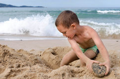 Child playing with sand on beach Stock Photos