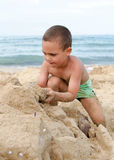 Child playing with sand on beach Stock Image