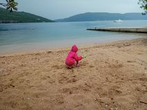 Cute little baby girl playing with the sand at the beach in a stormy weather stock photo
