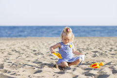Child playing with sand at the beach in summer Royalty Free Stock Photos