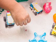 Child playing sand in bucket. Closeup of child hand playing sand in bucket royalty free stock photo