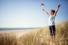 Child playing in sand dunes at the beach on summer vacation. Boy playing with windmill in sand dunes at the beach on summer vacation concept for freedom or the stock images