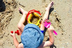Child playing with sand, shovel, bucket. Child on the beach playing with sand, shovel, bucket, build sand castle royalty free stock image