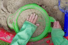 Child playing sand sieve sieving Stock Photos