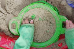 Child playing sand sieve sieving Stock Image
