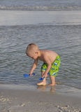 Child playing in the sand and surf. Stock Images