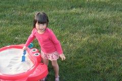 Child playing in sandbox stock image