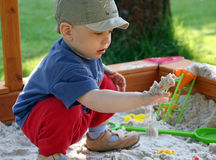 Child is playing in sandbox. Young boy plays in sandbox in the garden Royalty Free Stock Photos