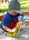 Child is playing in sandbox. Young boy plays in sandbox in the garden Stock Photos