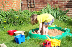 Child playing in a sandpit. Stock Photos