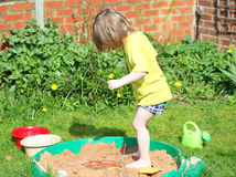 Child playing in a sandpit. Stock Image