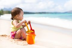 Child playing on sandy beach with a bucket and shovel. Small asian baby looks out over the breezy ocean as she thinks about what to build in the sand Stock Images