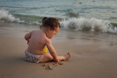 Child playing on a sandy beach, sunset time, small waves. Child playing on a sandy beach, sunset time, small waves royalty free stock images