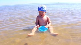 Child playing on the sandy beach stock video