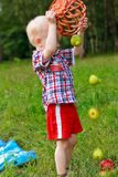 Child playing scattered of fruit with basket Royalty Free Stock Photography