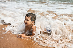 Child playing in the sea Stock Images