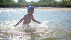 The child is playing at the sea, creating a splash of water. Entertainment and outdoor games stock footage
